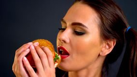 Woman eating hamburger. Girl wants to eat fast food. Woman eating hamburger. Girl wants to eat burger. Lunch in school cafeteria. Portrait of person with good royalty free stock photo
