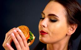 Woman eating hamburger. Girl wants to eat fast food. Woman eating hamburger. Girl wants to eat burger. Mom prepared dinner for her daughter. Portrait of person royalty free stock photos