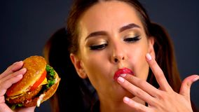 Woman eating hamburger. Girl wants to eat fast food. Woman eating hamburger. Girl wants to eat burger. Portrait person with good appetite have greedily dinner royalty free stock photo
