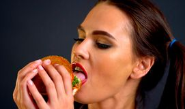 Woman eating hamburger. Girl wants to eat fast food. Woman eating hamburger. Girl wants to eat burger. Portrait of person with good appetite have greedily royalty free stock images