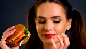 Woman eating hamburger. Girl wants to eat fast food. Woman eating hamburger. Girl wants to eat burger. Student consume fast food. Portrait of person with good stock photo