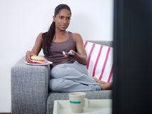 Woman eating hamburger and watching tv Stock Photo