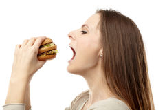 Woman eating hamburger Stock Photography