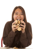Woman eating handful of cookies Royalty Free Stock Photo