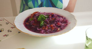 Woman eating healthy beetroot soup with parsley stock video footage