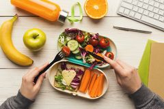 Woman eating healthy dinner from lunch box at her working table. Healthy snack at office workplace. Businesswoman eating organic vegan meals from take away lunch royalty free stock photography