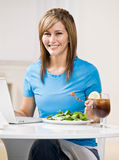 Woman eating healthy lunch while typing on laptop. Happy woman eating healthy lunch while typing on laptop stock photography