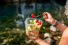 Woman eating healthy salad near the river Royalty Free Stock Photos