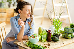 Woman eating healthy salad. Young and happy woman eating healthy salad sitting on the table with green fresh ingredients indoors Royalty Free Stock Photography