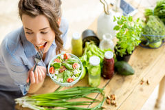 Woman eating healthy salad. Young and happy woman eating healthy salad sitting on the table with green fresh ingredients indoors Royalty Free Stock Photos