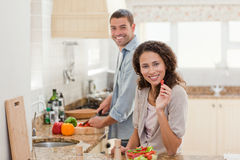 Woman eating while her husband is cooking Royalty Free Stock Photo