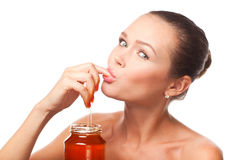 Woman eating honey Royalty Free Stock Image