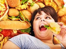 Woman eating hot dog. Overweight woman holding hamburger royalty free stock photo
