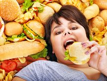Woman eating hot dog. Overweight woman holding hamburger stock images