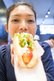 A woman eating a hot dog Stock Photography
