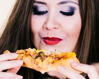 Woman eating hot pizza slice. Young woman eating hot fresh pizza slice. Delicious fast food meal. People, italian cuisine concept stock photography