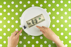 Woman eating hundred dollar bill for dinner Stock Photos