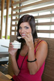 Woman eating an ice-cream. Close up of a pretty woman in pink eating an ice-cream in a fast-food restaurant Royalty Free Stock Photography