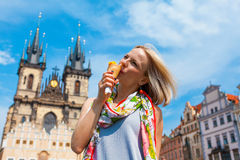 Woman eating ice cream on a background of Tyn Cathedral Stock Photography