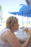 A Woman Eating an Ice-cream on a hot day Down at The Beach. A woman sitting down eating an ice-cream on a hot day with the beach in the background Royalty Free Stock Photo