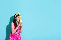 Woman eating ice cream isolated on blue background Stock Photography