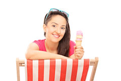 Woman eating ice cream seated on a sun longer Royalty Free Stock Photography