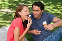 Woman eating ice cream while sitting with her friend Royalty Free Stock Photos