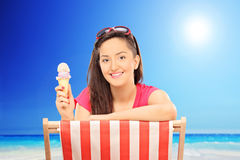 Woman eating ice cream on sunny day by the beach Stock Photography