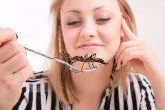 Woman eating insects with a fork in a restaurant Stock Photography