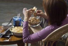 Woman eating junk food_1. Woman seated eating junk food stock image