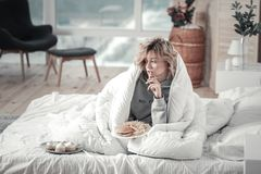 Woman eating junk food in her bed after breakup with boyfriend. Junk food. Blonde-haired stressed woman eating junk food in her bed after breakup with boyfriend royalty free stock photo
