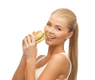 Woman eating junk food. Picture of healthy woman eating junk food stock photography