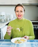 Woman eating at kitchen Stock Images