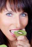 Woman eating kiwi Royalty Free Stock Images
