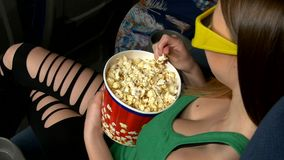 Woman eating large container of popcorn in cinema stock video