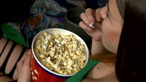 Woman eating large container of popcorn in cinema stock video footage