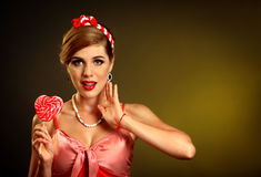 Woman eating lollipops. Girl in pin-up style hold striped candy. Royalty Free Stock Photos