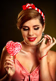 Woman eating lollipops. Girl in pin-up style hold striped candy. Stock Image