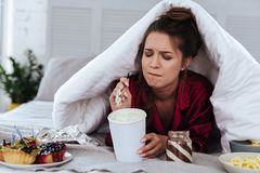 Woman eating a lot of desserts because of depression. Lots of desserts. Heartbroken woman eating a lot of desserts because of depression and huge stress at work royalty free stock image