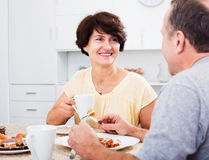 Woman eating lunch with husband. Glad senior women eating lunch and listening to her husband at home stock image