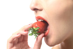Woman eating a luscious ripe red strawberry Royalty Free Stock Photo