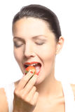 Woman eating a luscious ripe red strawberry Royalty Free Stock Photos