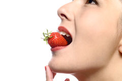 Woman eating a luscious ripe red strawberry Stock Photos