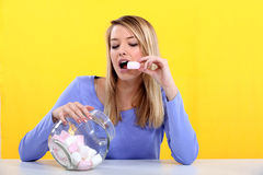 Woman eating marshmallow. From jar Royalty Free Stock Image