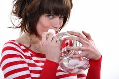 Woman eating marshmallow Stock Image