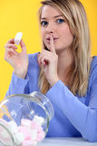 Woman eating marshmallows. Young woman eating marshmallows from a jar Stock Images