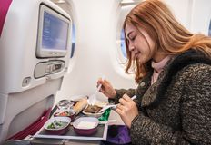 Woman eating meal on commercial airplane in flight time. Woman eating meal on commercial airplane in a flight time royalty free stock image