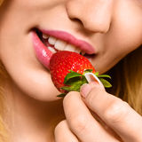 Woman eating mellow strawberry Stock Images