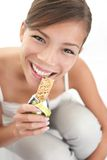 Woman eating muesli bar snack Royalty Free Stock Images