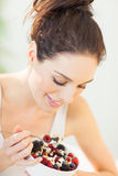 Woman Eating Muesli. Woman eating fresh made muesli breakfast dish with oats, fresh berries. Smiling healthy eating European girl Stock Photography